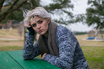 Sad woman looking off to side leaning on park table