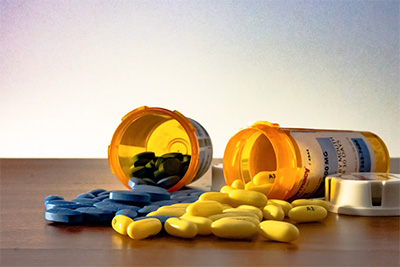 Two prescription bottles overturned with blue and yellow pills spilling out on the table with a white background representing America's epidemic of prescription drug overuse.