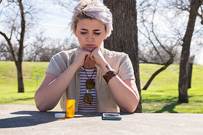 woman sits at table outside looking down at pill bottle and phone