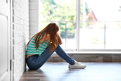 Sad teenage girl sitting near window in a room