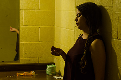 Woman leaning against wall in dim room holding pill