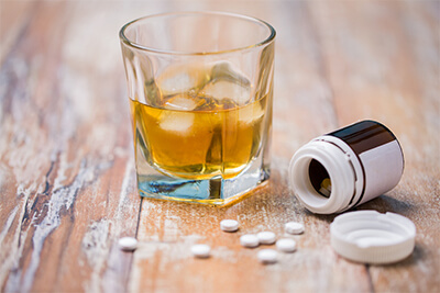 glass of alcohol and pills on table