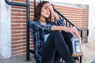 upset woman sits on top of stairs with alcohol bottle in hand