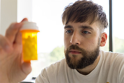 man looks seriously at bottle of pills closeup