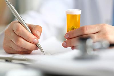 Female doctor hand hold prescription bottle of pills and write prescription at worktable.