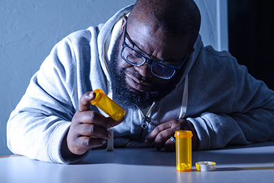 Man sitting at table looking at pill bottle in hand