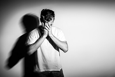 sad man with hands on face in sadness on white background black and white photo free space