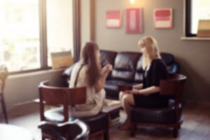 psychologist consulting a woman client indoors discussion therapy, blurred defocused view two women talk