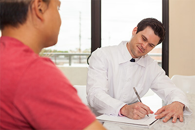 Male medical physician at a table with male patient taking notes