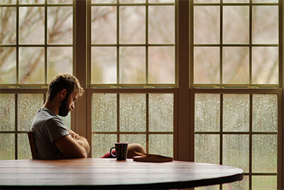 man sitting at table looking down