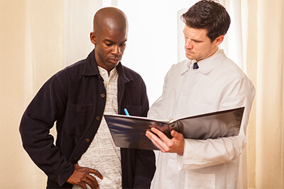 Male black men looking over notes with male white medical physician