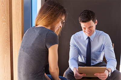 male medical physician sitting down with female patient review patient chart