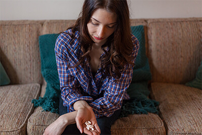 Woman looks down at pills in her hand