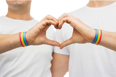 close up of happy male couple wearing gay pride rainbow awareness wristbands showing hand heart gesture